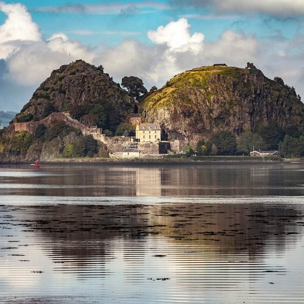 Dumbarton Castle on its rock with a calm River Clyde in the foreground