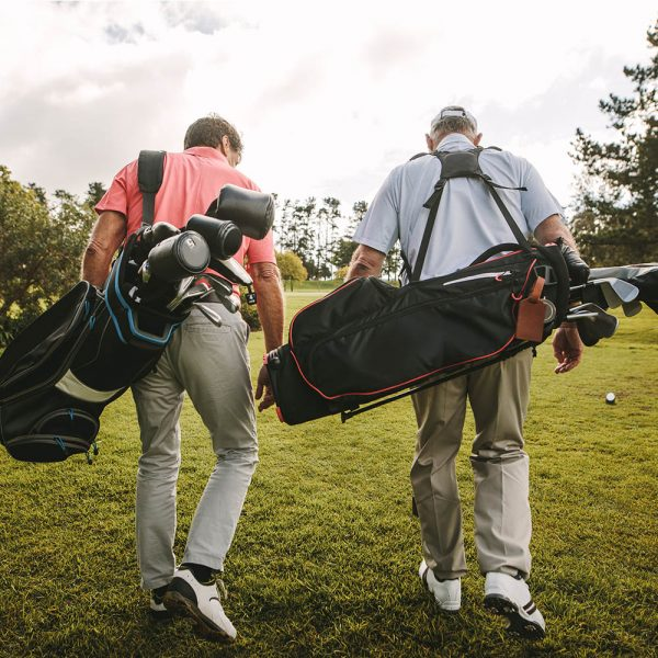 Two male golfers walking with their golf bags over their shoulders