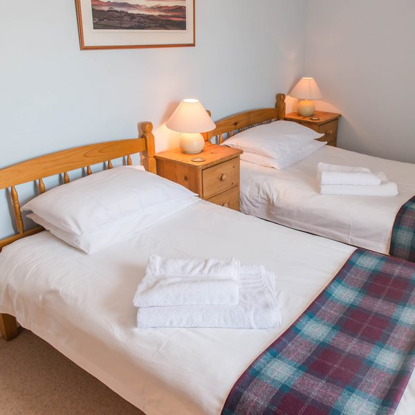 Twin beds with tartan throw in the Ballat Smithy Cottage