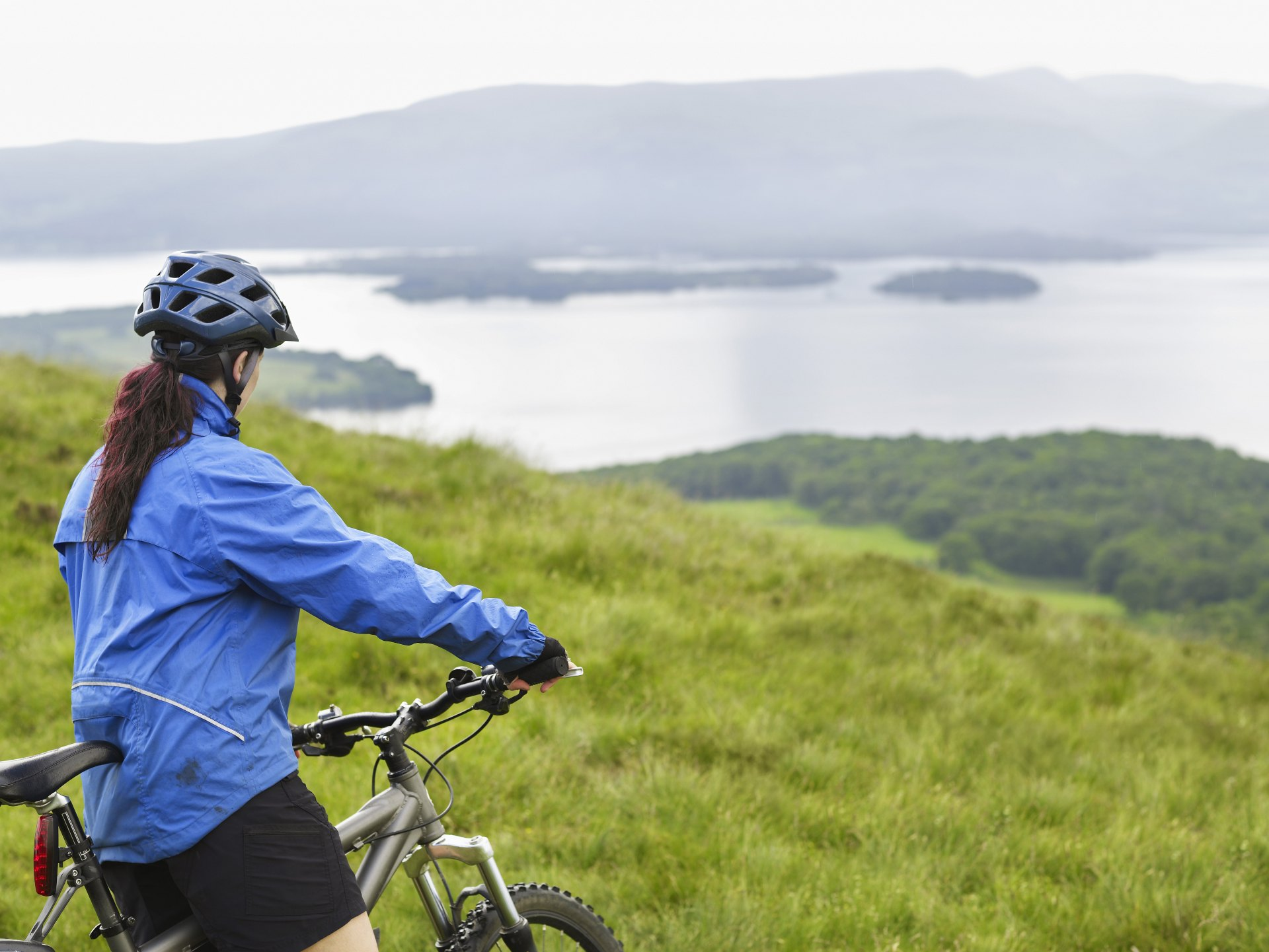 Loch Lomond Cycling, lady mountain biking above loch lomond