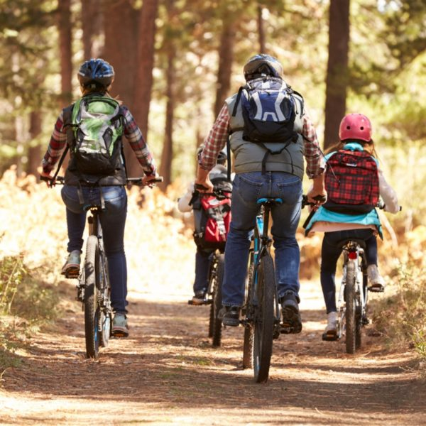 A family cycling through a Scottish forest