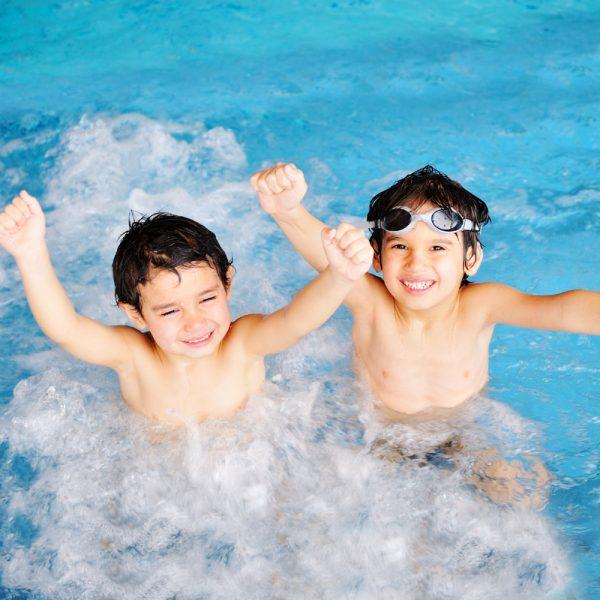 Two kids splashing in an indoor swimming pool